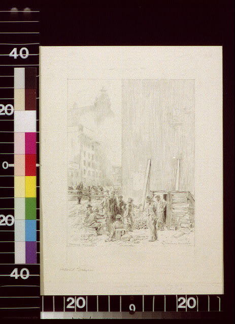 [Group of men standing beside a shack; tall buildings in the background]