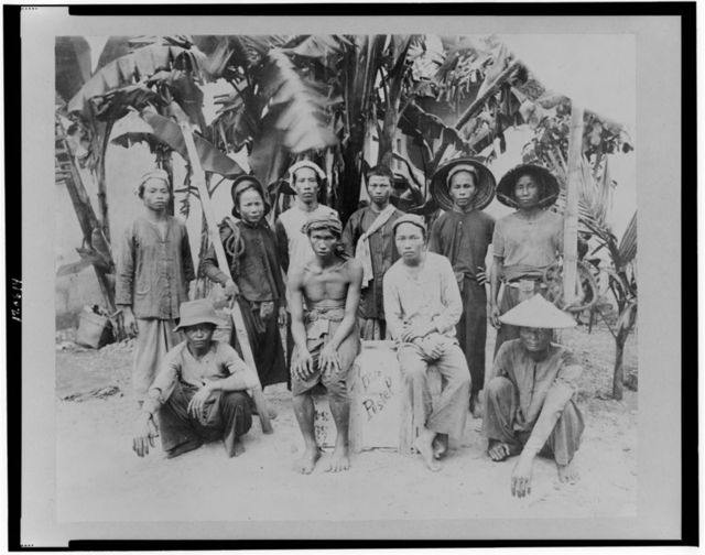 [Group of ten workers posed by palm trees, Saigon, South Vietnam]