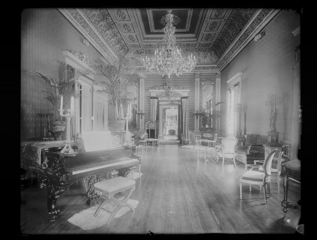 [Interior view of a large hall with piano, chairs, small tables, and sofas, chandeliers, ornate ceiling, and of a fireplace in the rear drawing room in the Corcoran House, formerly at the corner of H Street and Connecticut Avenue NW, Washington, D.C.]