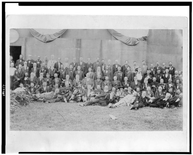 [John M. Harlan seated in the center of a large group of men posed for a portrait]