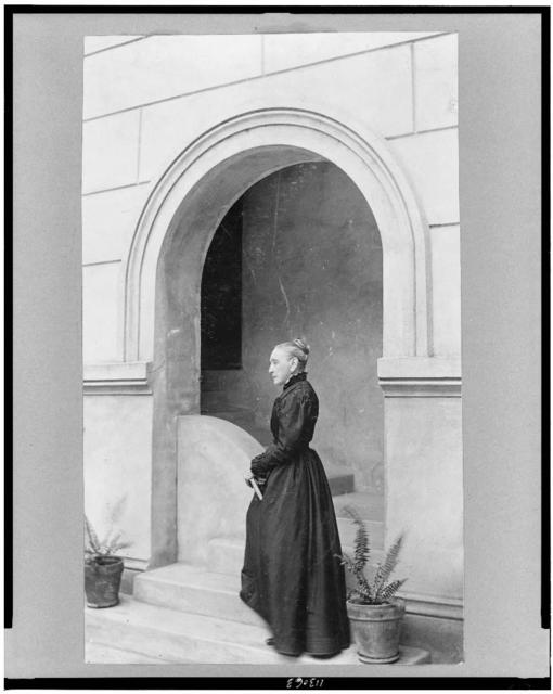 [Josephine Louise Monnier Newcomb, full-length portrait, standing on step of entrance to building, facing left]