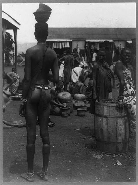 Native market of the Kavirondo tribe - woman in foreground wears tassel which is the tribal insignia of a married woman; Anklets are of telephone wire, Victoria Nyanza, Tanganyika, Africa.