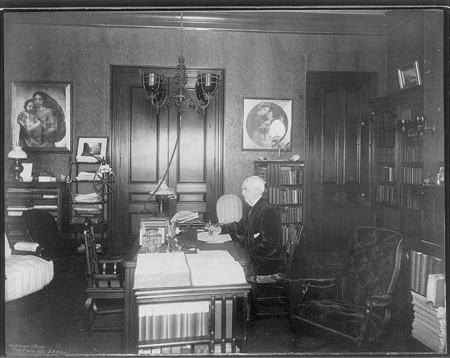 [Oliver Wendell Holmes, 1809-1894, half-length portrait, seated at desk, facing left, in his study]