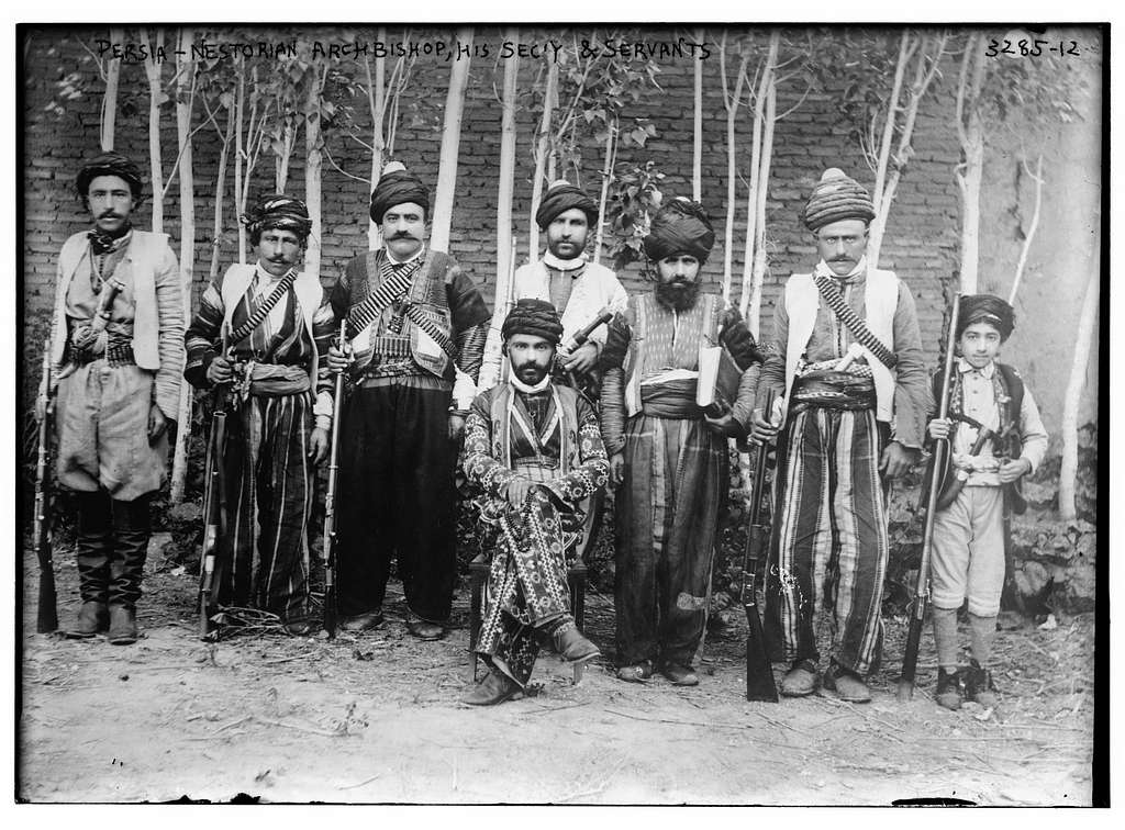 Shemasha (Deacon) Ishai d'Mar Shimun (half-brother of Patriarch Mar Rowel and father of the next Patriarch of the Church of the East, Mar Benyamin), seated, with secretary and servants, possibly in Urmia, Persia or Turkey