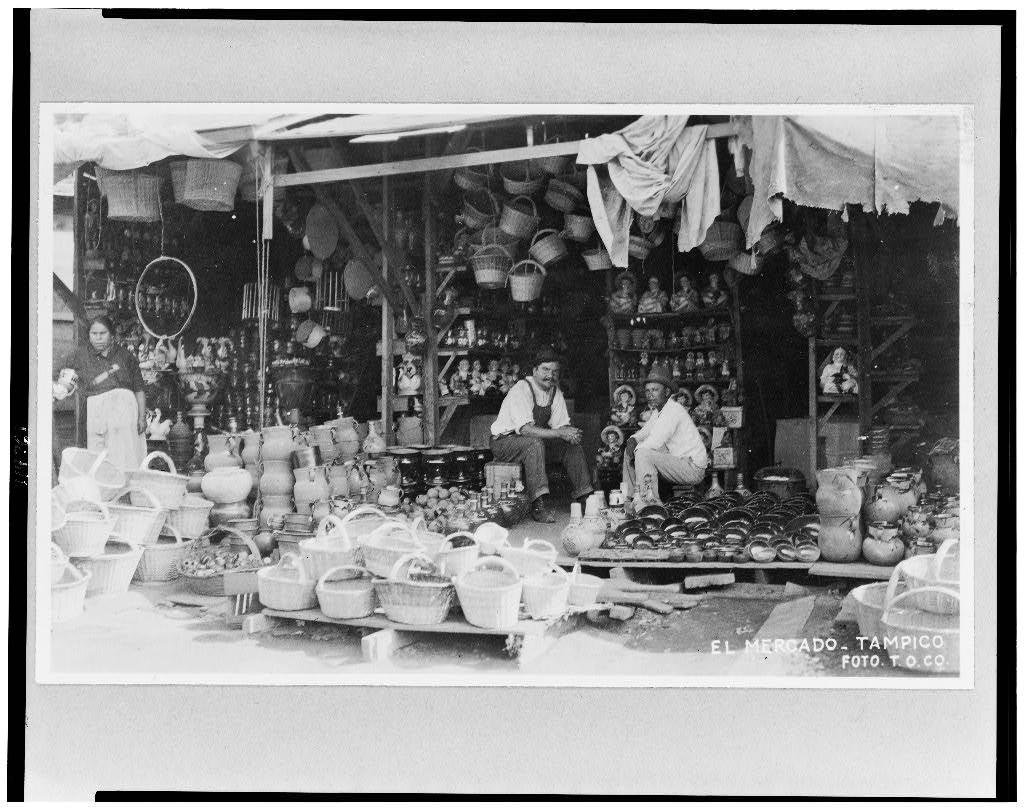 [Store, with baskets and pottery in foreground, Tampico, Mexico
