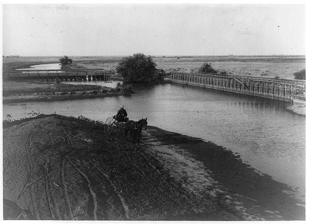 [The Calloway Canal showing the weirs at Poso Creek with woman(?) in horse-drawn cart in foreground]