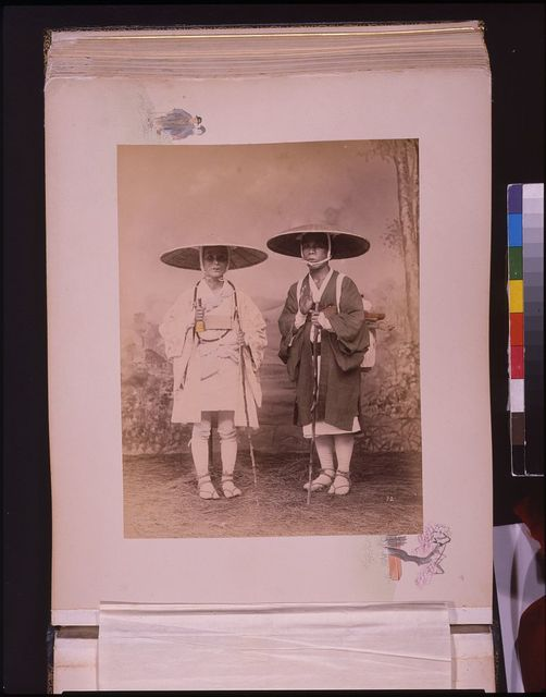 [Two travelers with staffs, wearing hats, studio portrait]
