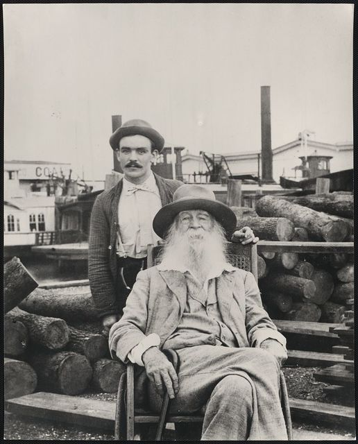 [Walt Whitman, three-quarter length portrait, seated, facing front, with his nurse Warren Fritzenger, standing, and a pile of logs behind him, on the wharf, probably near his Mickle Street house in Camden]