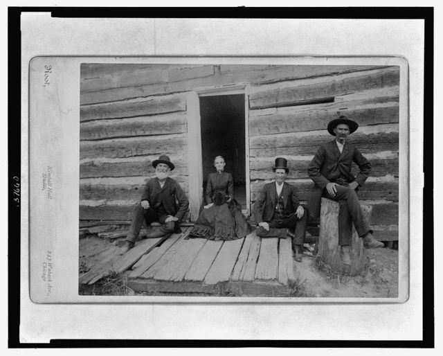 A partial view of the Lincoln cabin with open door and group of four including Mr. Thomas Lincoln's grandson John J. Hall / Root, Kimball Hall Studio, 243 Wabash Ave., Chicago.