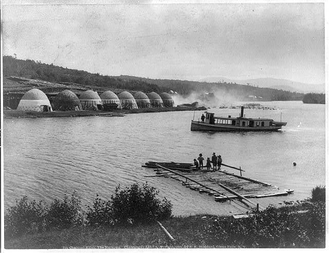 Charcoal kilns, the narrows, Chateaugay Lake, [Adirondack Mts., N.Y., small steamer and floating dock in foreground]
