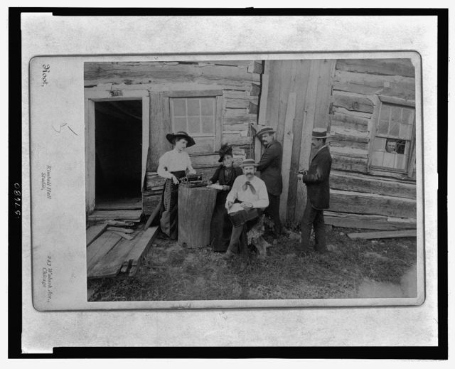 Front view of a portion of the Lincoln cabin with a group composed of Mrs. Norah Gridley, Miss Mary Coleman, the typewriter, the brothers Megar, architects, and Mr. Stille, and showing young Hall a great grandson of Tho Lincoln looking through the window of the east room of the cabin / Root, Kimball Hall Studio, 243 Wabash Ave., Chicago.