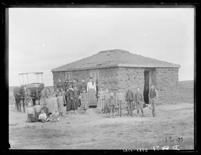 Students and teachers in front of sod schoolhouse, Custer County, Nebraska.