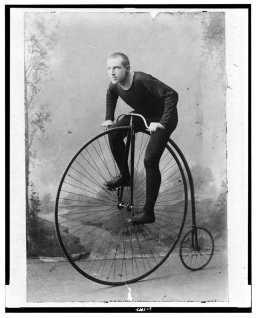 [William Martin, champion six-day bicycle rider of the world, full-length portrait, facing left, on bicycle with large front wheel and small rear wheel]