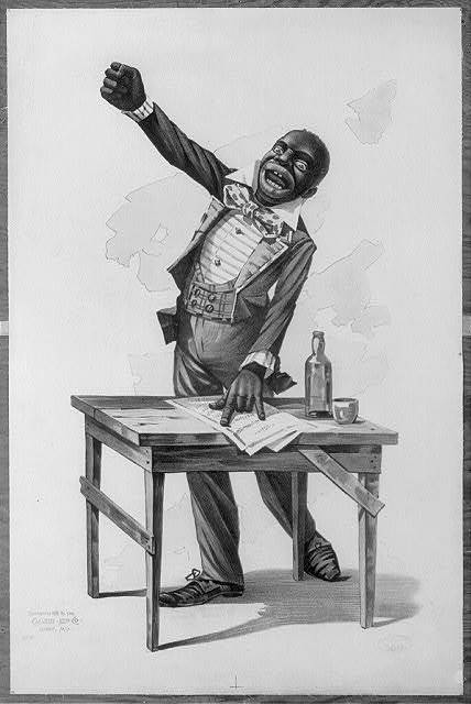 [African American, standing at desk, with one hand resting on papers and one hand raised]
