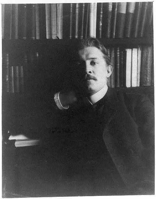 [Bertram G. Goodhue wearing suit in library, seated]