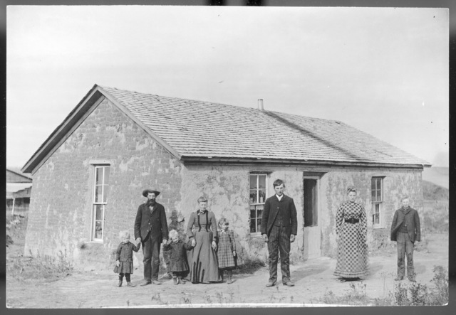 Family in front of a sod house with a frame roof.