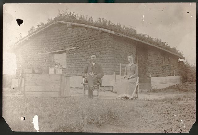 Group of children with four adults in front of sod house
