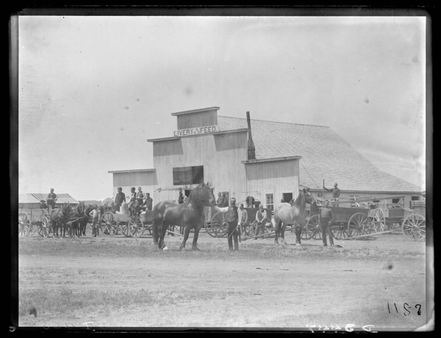 Group of men and wagons in front of livery barn at Callaway, Custer County, Nebraska.