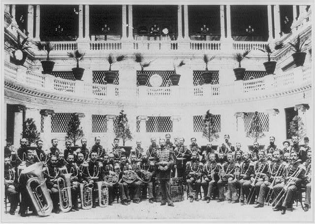 [John Philip Sousa, 1854-1932, full-length portrait, standing, facing left, with the U. S. Marine Corps band at the Palace Hotel, San Francisco]