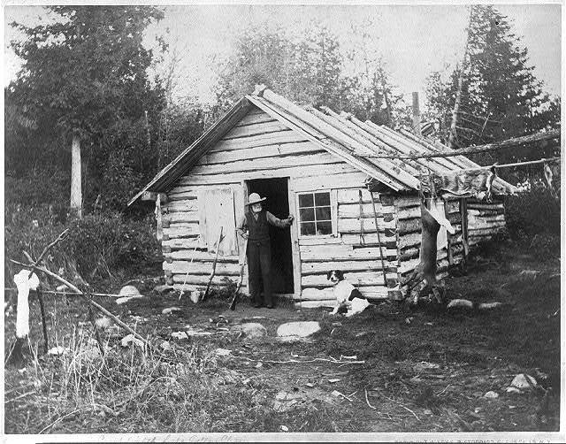 [Man with shotgun at doorway of cabin and a deer hanging from pole at camp, Eighth Lake, Fulton Chain, Adirondack Mountains, N.Y.]