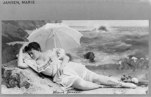 [Marie Jansen, full-length portrait, in studio beach scene, facing left, smoking cigarette and holding umbrella]