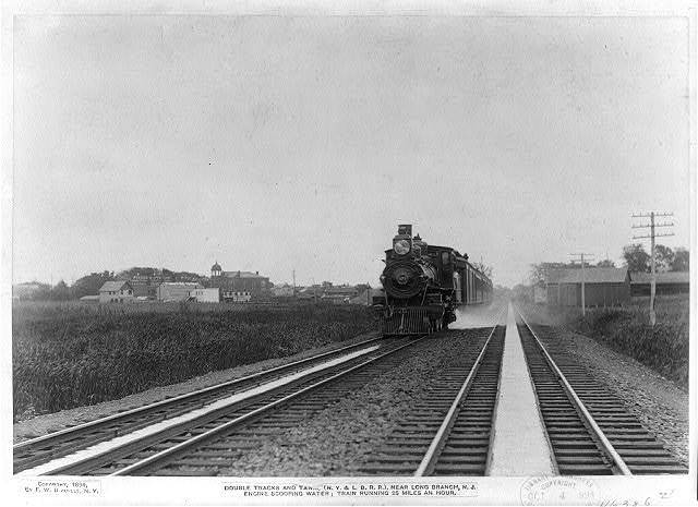 Double tracks and tanks (N. Y. & L. B. R. R.) near Long Branch, N. J. engine scooping water; train running 25 miles an hour.