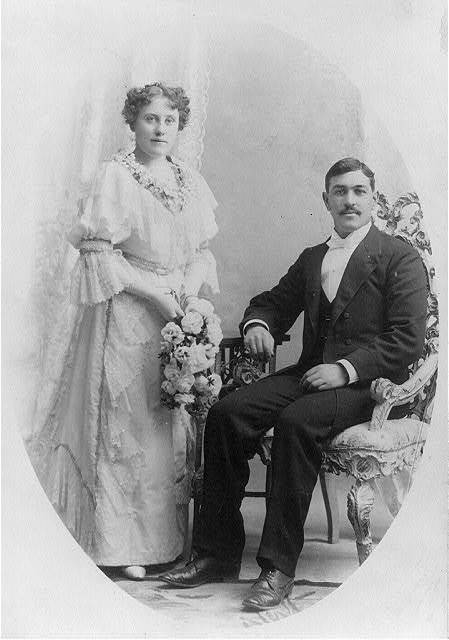 [Wedding picture, man seated and woman holding flowers and standing]