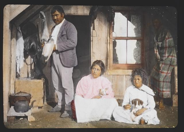 Bella - Maori woman with husband and child and 2 dogs in front of home at Hot Springs