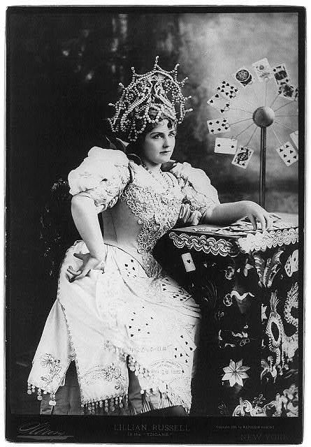 """[Lillian Russell, 1861-1922, three-quarters length, seated, facing right; with cards at table, in the """"Tzigane"""" (fortune teller)]"""