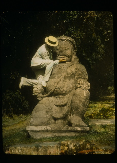 Man in straw hat standing on Buddhist idol at ruins of Borobudur