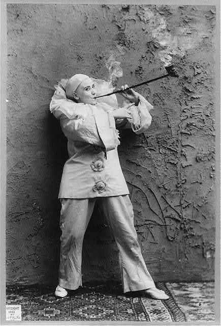 Pilar Morin as clown/mime: Full length, standing, facing right; smoking pipe