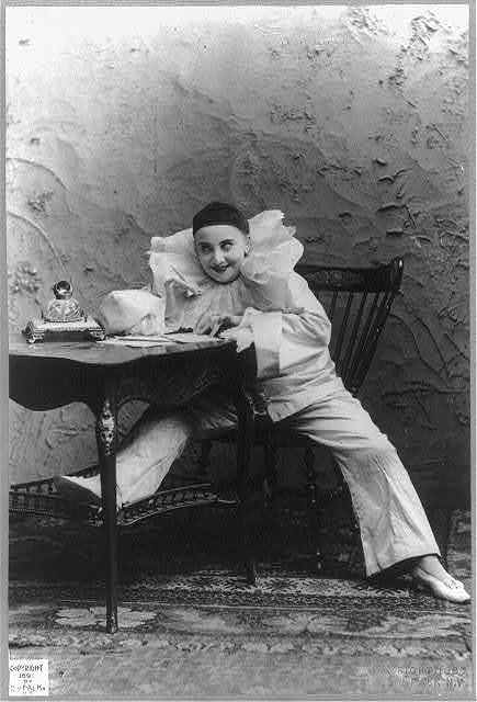 Pilar Morin as clown/mime: full lgth., seated at table