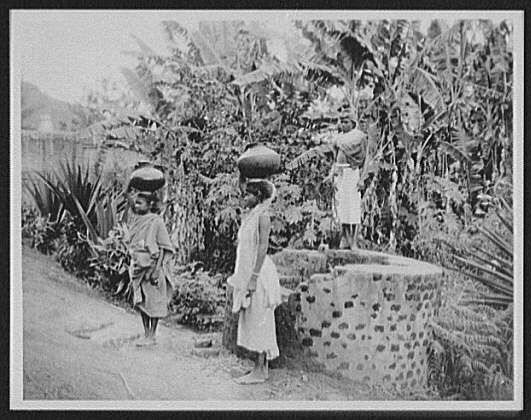 Two Tamil women with large pots on their heads at the well of the Maria Watta Tea Estate