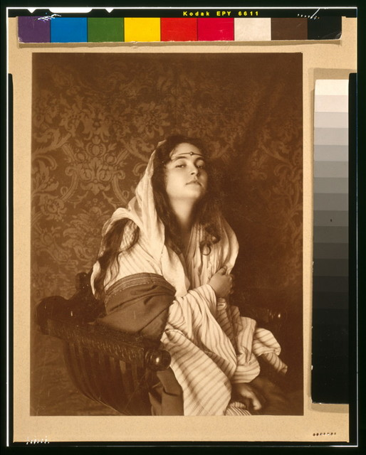 [Young woman (Nancy Lovis (Kraft)) in Middle Eastern costume with jeweled headband, seated]