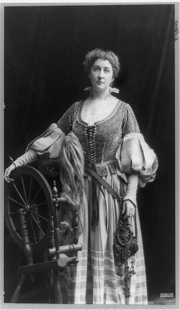 [Emma Eames, three-quarter length portrait, standing, facing front with right hand on spinning wheel]