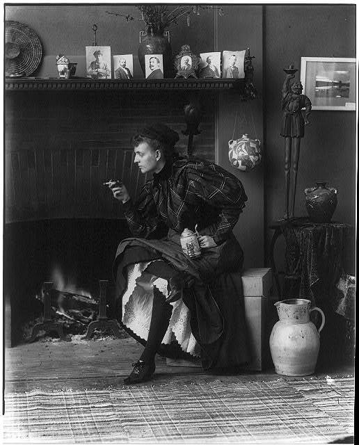[Frances Benjamin Johnston, full-length portrait, seated in front of fireplace, facing left, holding cigarette in one hand and a beer stein in the other, in her Washington, D.C. studio]