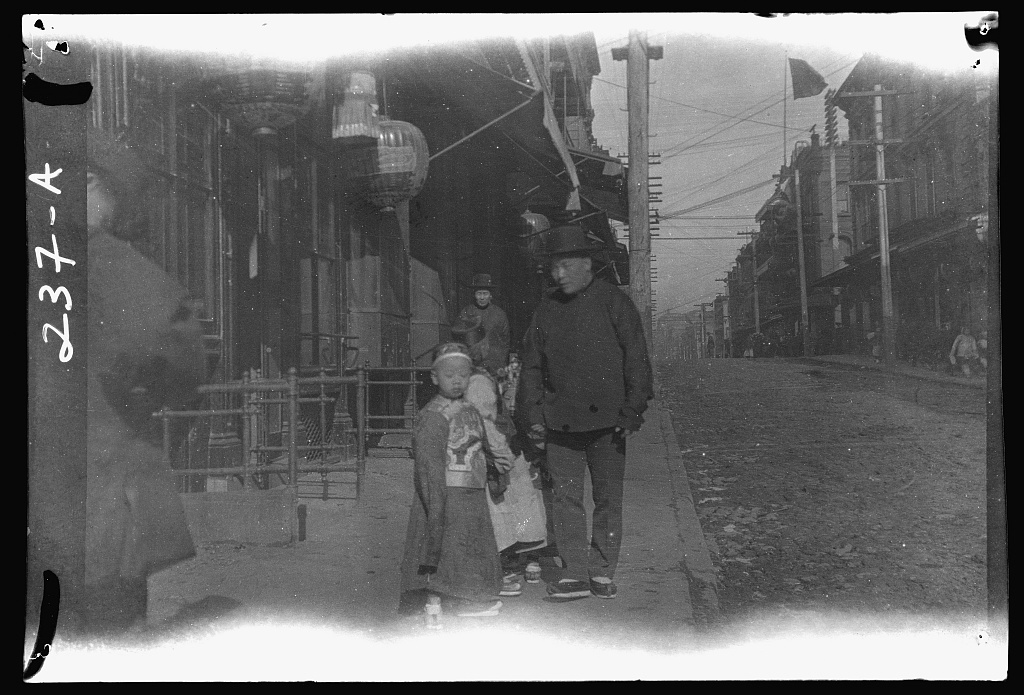 Man and children walking down a street, Chinatown, San Francisco