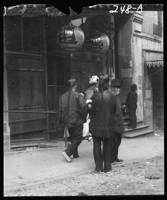 Men standing or walking down a sidewalk, Chinatown, San Francisco