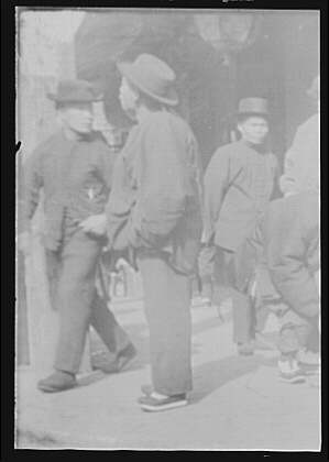 Men standing or walking on a street, Chinatown, San Francisco