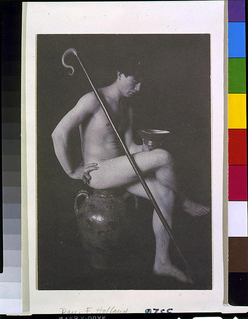 [Nude man in studio with shepherd's crook, seated on urn]