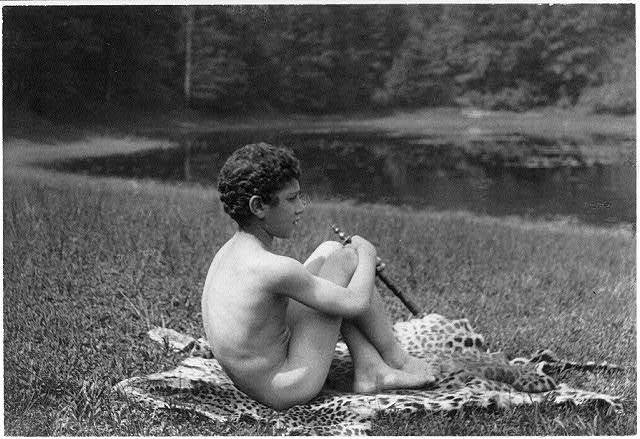 [Nude youth with pipe seated on leopard skin, in nature]