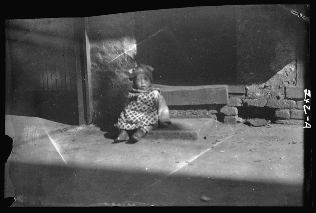 Small child sitting on a doorstep, Chinatown, San Francisco
