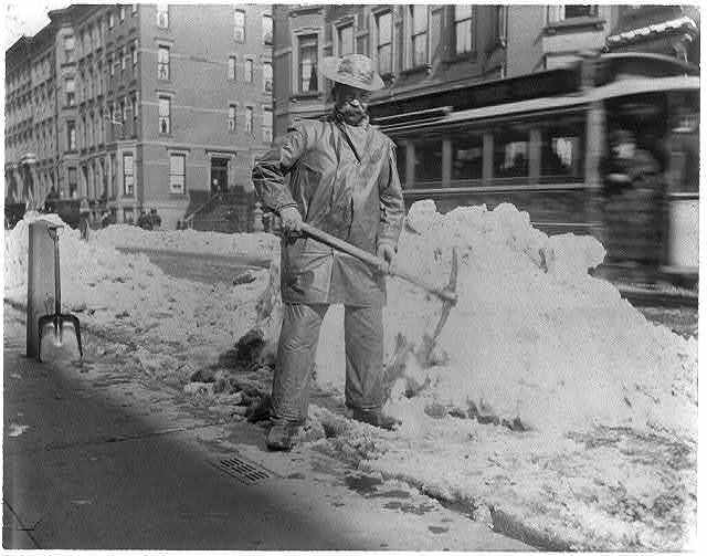[Street types of New York City: Street cleaner with pick ax standing in front of pile of snow]