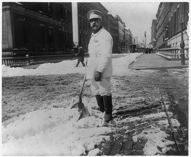 [Street types of New York City: Street cleaner with rubber boots shoveling snow]