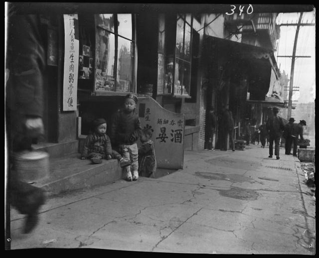 Three children in front of a cellar door, Chinatown, San Francisco