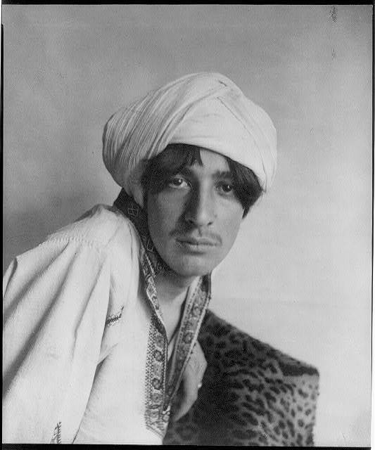 [Young man in Middle-Eastern costume, with turban and leopard skin, in studio]