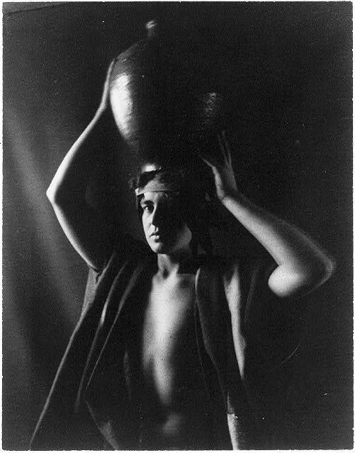 [Young man in North African costume with urn on head, in studio]