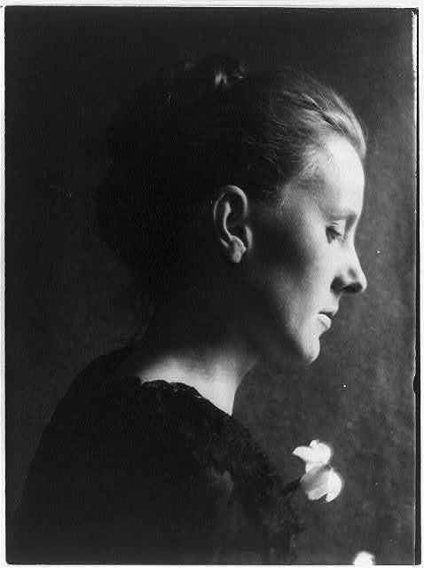 [Young woman in black with flower, profile]