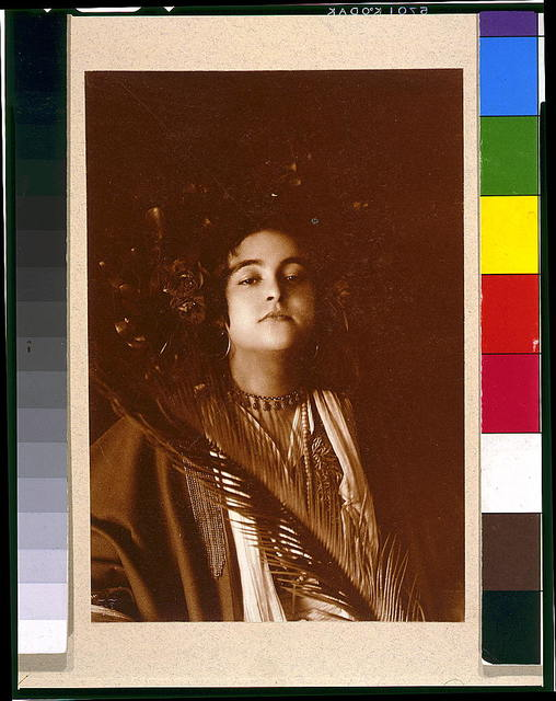 [Young woman (Nancy Lovis (Kraft)) in Middle Eastern costume, with floral headdress and palm frond, head-and-shoulders portrait, facing front]