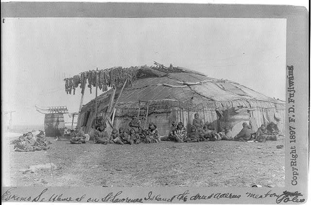 [Group of Eskimos outside large circular house on St. Lawrence Island; walrus meat drying on poles]